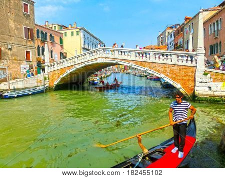 Venice, Italy - June 06, 2015: Unidentified man rows gondola on June 06, 2015 in Venice, Italy. Venice is situated across a group of 117 small islands that are separated by canals and linked by bridges.