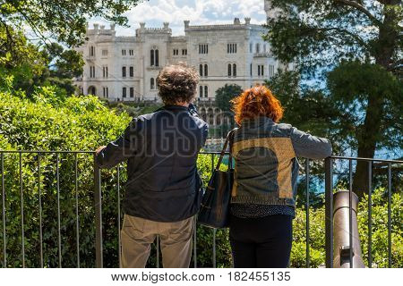 Adult couple admiring a sea castle. Tourists sightseeing.