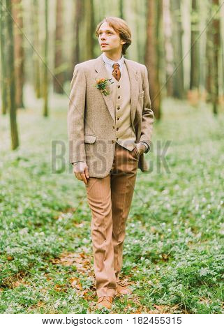 The full-lenght portrait of the man with blond hair in vintage suit looking at the sky and the mini-bouquet is pinned on the jacket. The green forest location