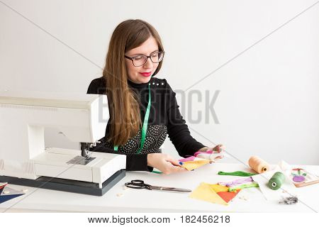 needlework and quilting in the workshop of a young woman tailor - young woman tailor sitting behind a desk and holding in her hand stitched on the sewing machine pieces of brightly colored fabric
