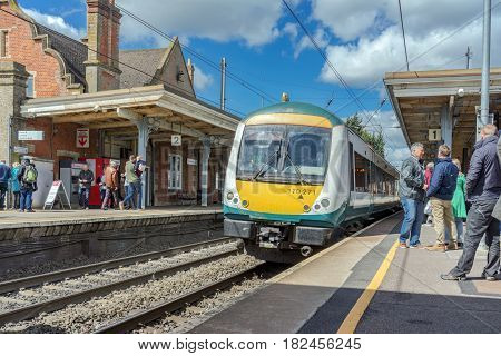 Stowmarket, UK. 17th April 2017. People are on platforms at Bury St Edmunds awaiting their onward departures. A Class 170 turbostar DMU train is about to depart for Ipswich.