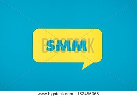 The SMM abbreviation cut-out in the yellow comic cloud on the blue background.