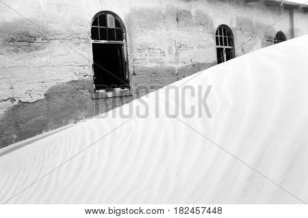 Black and white picture of an abandoned house in the ghost town of Kolmanskop, Namibia, Africa.