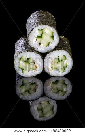 Sushi maki with cucumber on a black background with reflection. Asian food