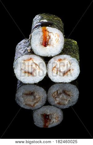 Sushi maki with eel on a black background with reflection. Asian food