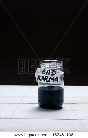 Bad Karma - an inscription on the label of a glass jar with a liquid of black color on a black and white background