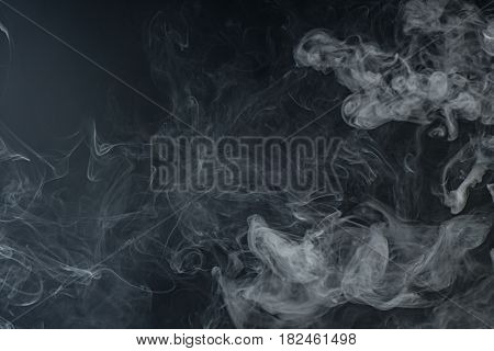 White Smoke On Black Background Occupying Two Thirds Of The Overall Image.
