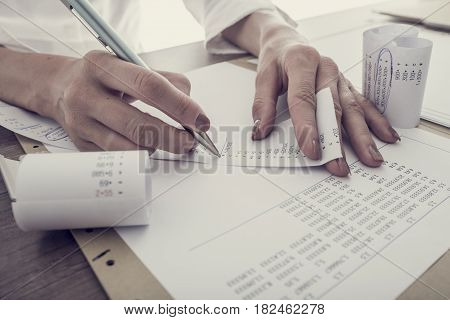 Retro toned image of accountant summing up the numbers writing on a printout receipt while making financial report.