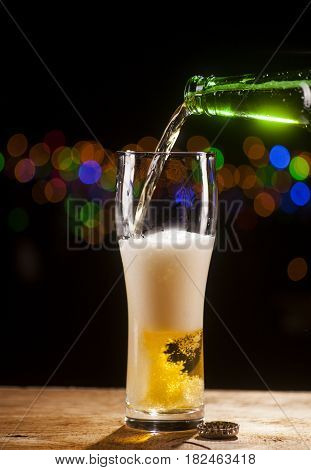 Beer Is Pouring Into Glass On Bar Lights Background