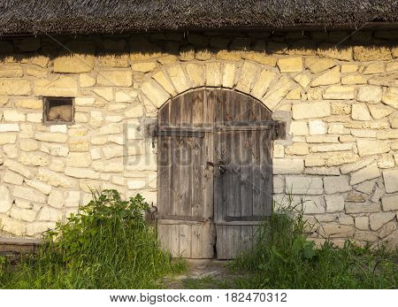 Stone shed under the thatched roof. Locked wooden door. Old Ukrainian architecture.