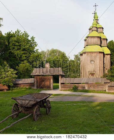 Ancient wooden church (XVIII century) from the Central Ukraine in the open-air Museum of Folk Architecture near Kyiv. Old wooden cart on the green grass in the foreground.