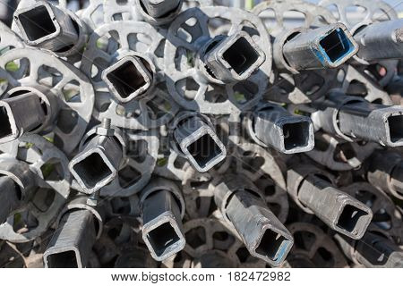 Pile of disassembled metal scaffolding tubes on the construction site. Close-up.