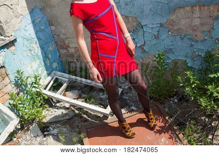 Young attractive woman in a red short dress posing near the old ruined building.
