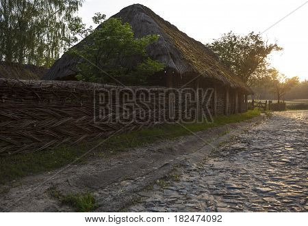 The road paved with stones in the Ukrainian village. Wicker fence and straw thatched roof along the road. Museum of Folk Architecture near Kyiv.