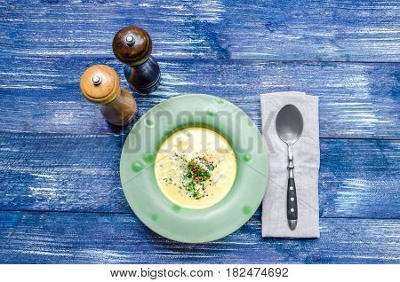 Yellow Cheese Soup With Meat And Herbs, In A Green Plate, With A Spoon And Spices On A Blue Denim Ba