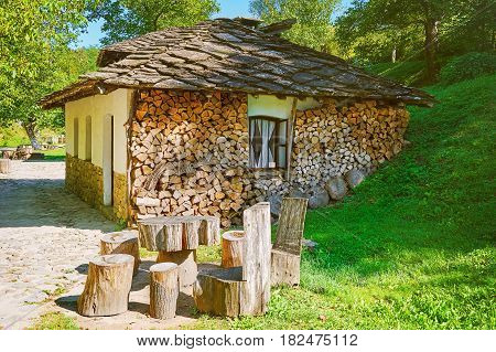 Small House in the Settlement with Stacked Firewood near the Wall