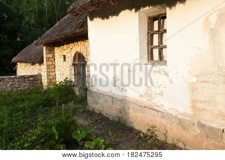 Old traditional Ukrainian house built in wattle and daub technique and sandstone shed. Thatched roof.