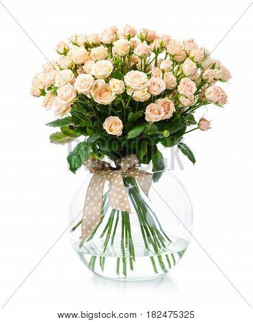 Bouquet of cream roses in glass vase over white background