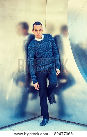 Young American Man wearing blue patterned knit sweater black pants leather shoe standing by silver wall with reflections in New York.