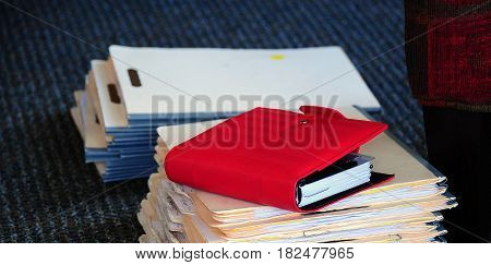 Client work files on the floor of a busy business office indoors.