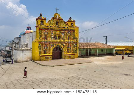 San Andres Xecul Guatemala - April 29 2014: The colorful church of San Andres Xecul and three local Mayan woman walking on the street in Guatemala