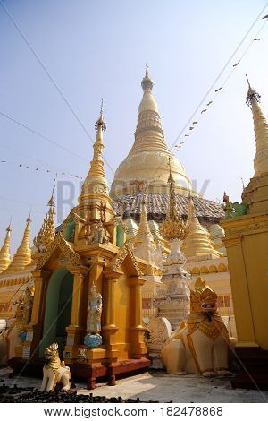 Golden Shwedagon Pagoda shining in sunlight surrounded by Buddhist stupas and temple figurines.