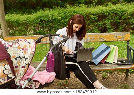 A woman with baby carriage and shopping bags working with tablett in the park while sitting on a bench.