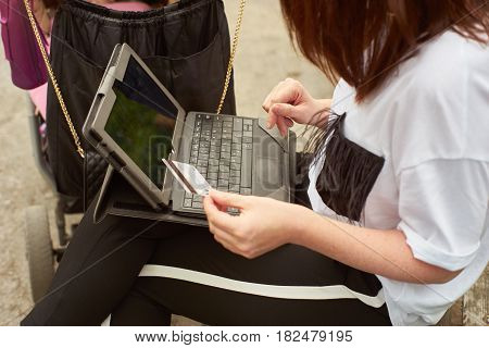Crop shot of a woman with baby carriage holding in her hand a credit card and making online shopping with tablett in the park while sitting on a bench.