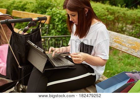 A woman with baby carriage holding in her hand a credit card and making online shopping with tablett in the park while sitting on a bench.