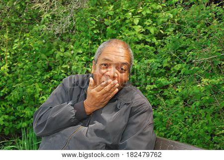 African american male expressions sitting on a park bench outdoors.