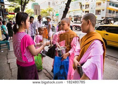 YANGON, MYANMAR-MARCH 3, 2017: Unidentified young women novice monks walking morning alms in Yangon, Myanmar on March 3, 2017.
