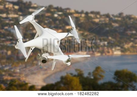 Unmanned Aircraft System (UAV) Quadcopter Drone In The Air Over The Ocean Coastline.