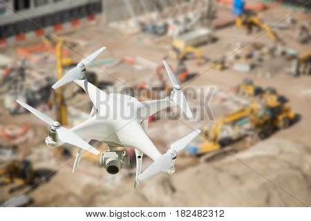 Unmanned Aircraft System (UAV) Quadcopter Drone In The Air Over Construction Site. poster