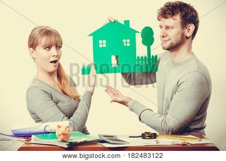 Design property family ownership real estate concept. Young couple arguing about future. Man and woman holding house model discussing plans.