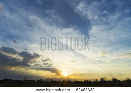 Golden sunrise and blue sky over silhouette of residential community houses and park large skyscape with space for text