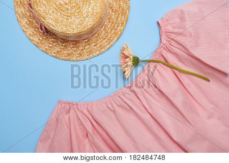 Top view of an off-the-shoulder swing blouse with straw hat on blue background. Summer outfit with flower. Female fashion
