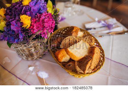 Basket with freshly baked rolls. Decorative basket at the wedding.