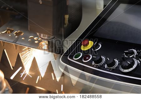 The CNC laser cut machine while cutting the sheet metal with the sparking light and the control panel .The hi-precision sheet cutting process by laser cut
