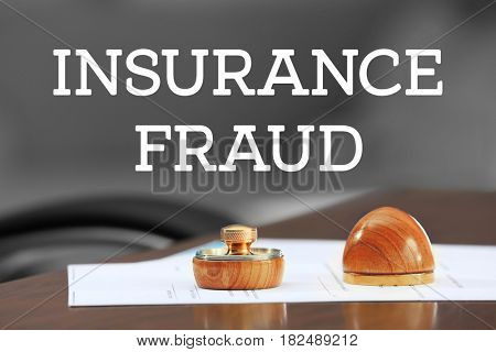 Insurance fraud concept. Stamp, ink pad and document on table
