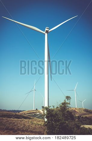 Eco power wind turbines generating electricity with clear blue sky background and grassland. Green earth concepts. Landscape with windmills for electric power production renewable energy source.