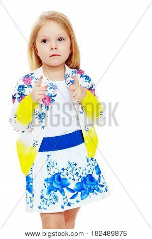 Pretty little blonde girl in a short summer skirt with Russian national ornament.