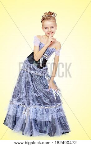 Slender little girl , with beautiful hair on his head, elegant long Princess dress.Girl holding finger at her lips. The gesture quiet.On a yellow gradient background.