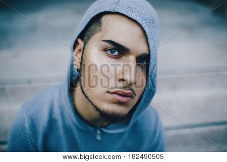 Conceptual art portrait of spooky weird beautiful handsome young middle east brunette blue eyes man face with beard piercing in ears wearing blue hoodie looking in camera