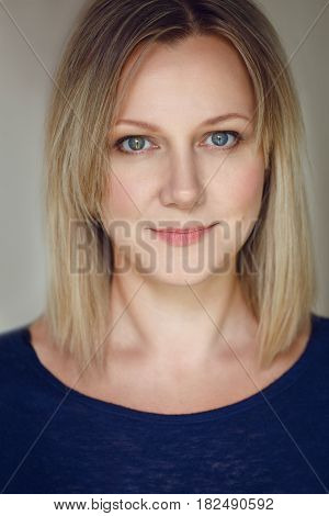 Closeup portrait of beautiful young middle age Caucasian woman in blue shirt looking in camera with long blonde hair bob and blue eyes flirty look