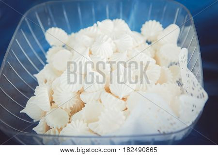 Closeup shot of white fresh tender marshmallow zephyr in a glass plastic bowl dish on table sweet snack food for party
