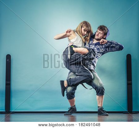 Two modern dancers couple teen woman and man dancing on blue. Urban lifestyle. Hip-hop generation.