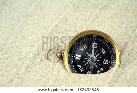 Old compass buried in sand close up image