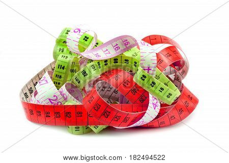Various entangled measuring tape on white background