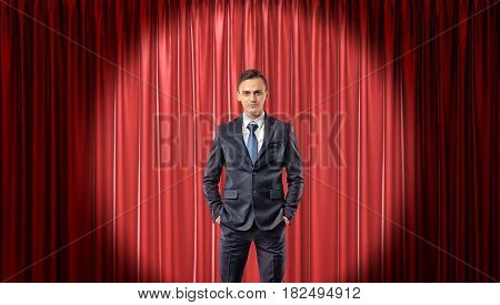 A confident businessman standing in front view in the spotlight with a red stage curtain behind him. Show business. Presentations. Opening night.