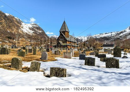 Roldal Stave Church (Roldal stavkyrkje) with snow graveyard foreground Norway